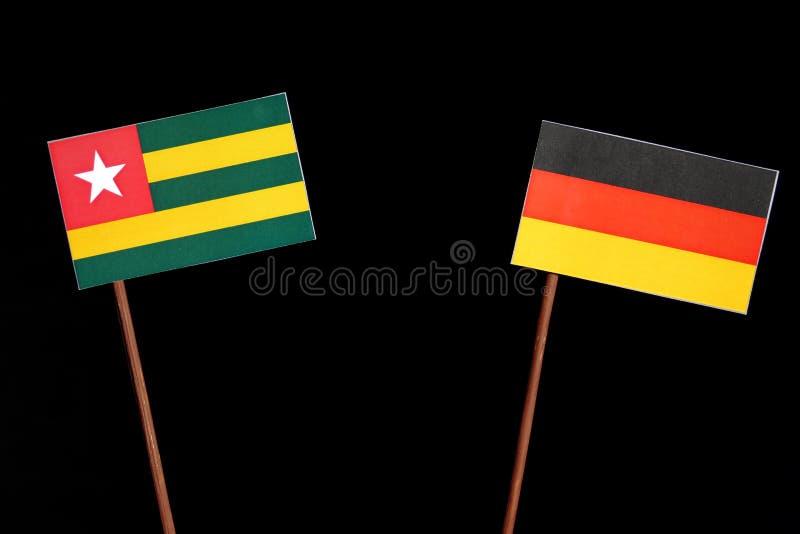 Togo-Flagge mit deutscher Flagge auf Schwarzem lizenzfreie stockfotografie