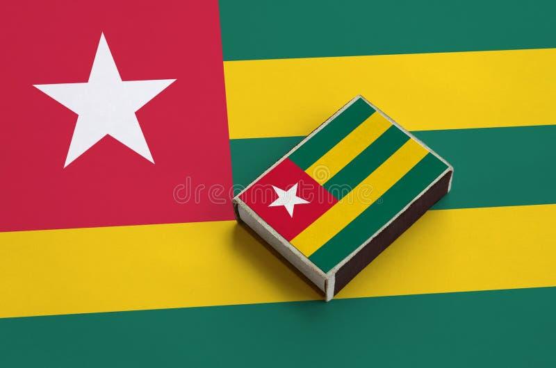 Togo-Flagge wird auf einer Streichholzschachtel dargestellt, die auf einer großen Flagge liegt stockfotografie