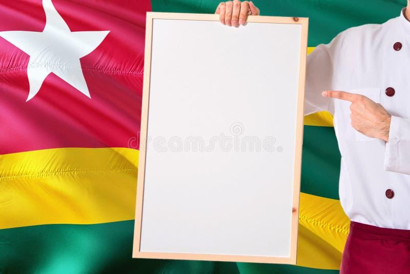 Togolese Chef-kok die leeg whiteboardmenu op de vlagachtergrond van Togo houden Kok die eenvormige richtende ruimte voor tekst dr stock afbeeldingen