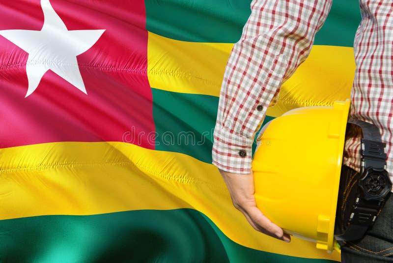 Togolese inżynier trzyma żółtego zbawczego hełm z machać Togo chorągwianego tło Budowy i budynku poj?cie zdjęcie royalty free