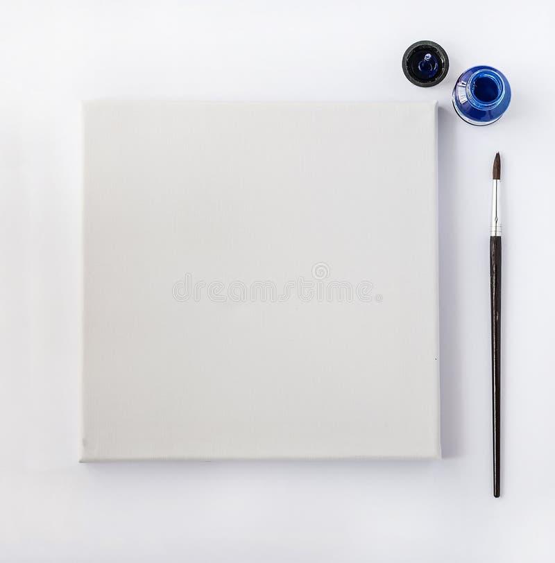 Toile avec le pinceau et encre, vue supérieure sur le blanc photos stock