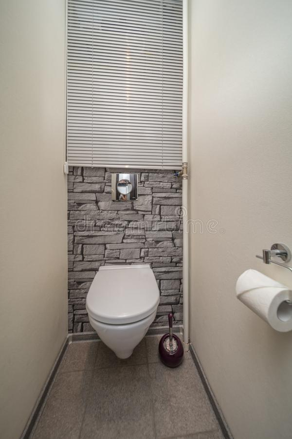 Restroom with toilet. Toilet bowl in the bathroom. Restroom with grey wall decoration stock photography