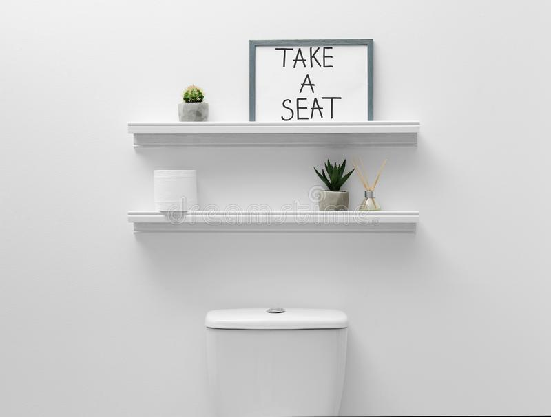 Toilet bowl, decor elements and funny sign near white wall. Bathroom interior royalty free stock image