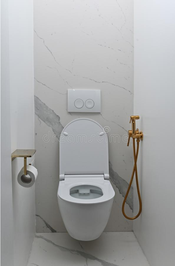Toilet bowl in modern bathroom. modern toilet with gold accessories royalty free stock photo