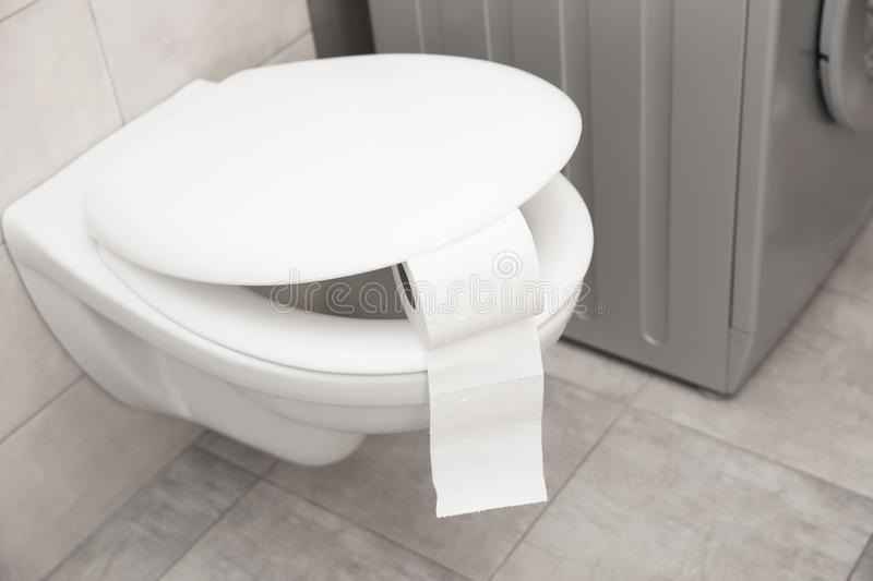 Toilet bowl with paper roll stock photos