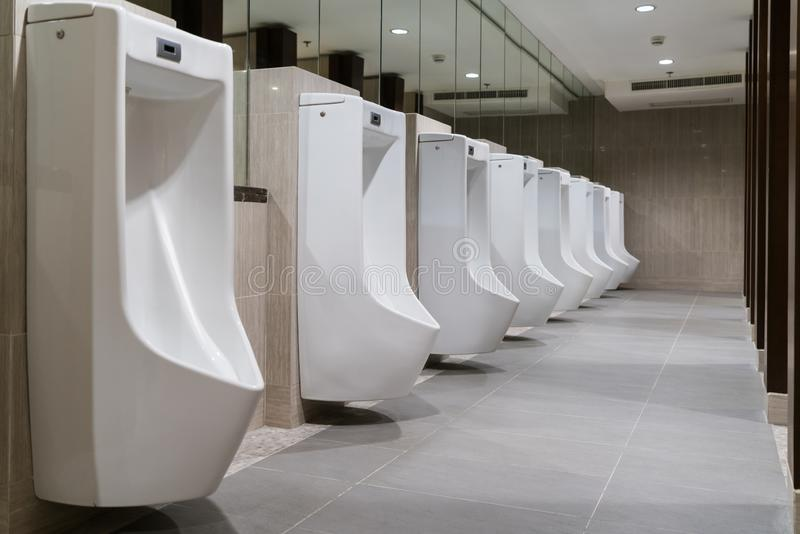 The toilet of man with Row of modern white ceramic urinals in public toilet or restaurant or hotel or shopping mall, interior royalty free stock images