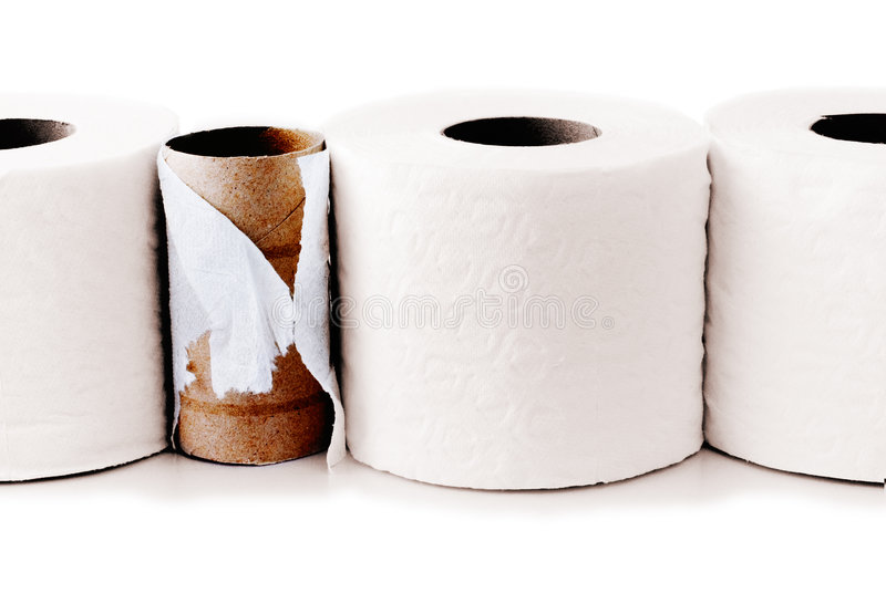 Toilet paper rolls in a row. With a used up one among them royalty free stock photography