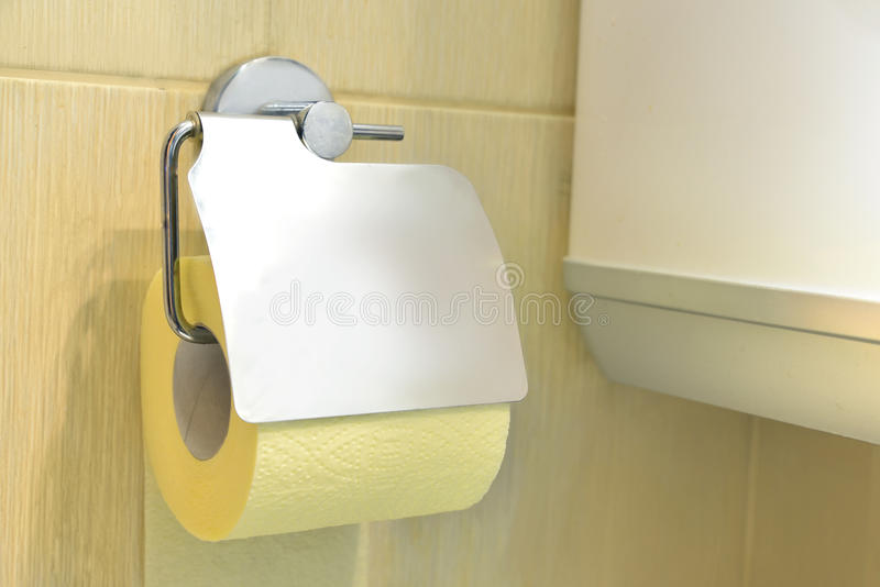 Toilet paper. Toilet yellow paper and toilet paper holder stock images