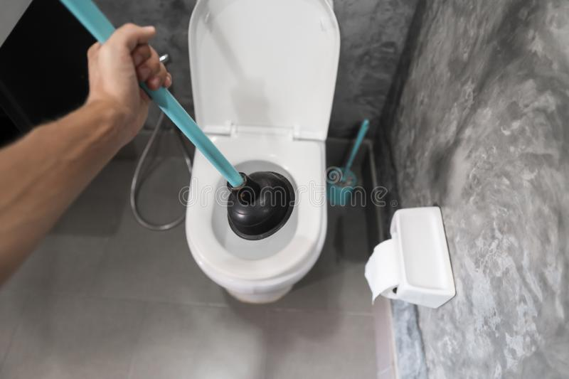 Toilet repair by hand with a Toilet Plunger. Plumbing. A plumber uses a plunger to unclog a toilet. Toilet Plunger. Toilet repair by hand with a Toilet Plunger royalty free stock image