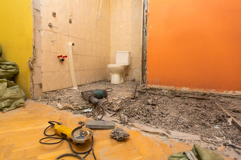 Toilet room or restroom with old toilet bowl and construction tools - perforator and angle grinder are in apartment that royalty free stock photos
