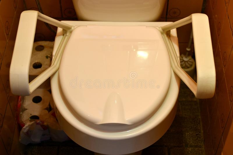 Toilet seat closed for disabled people. With revolving handles mobile royalty free stock images