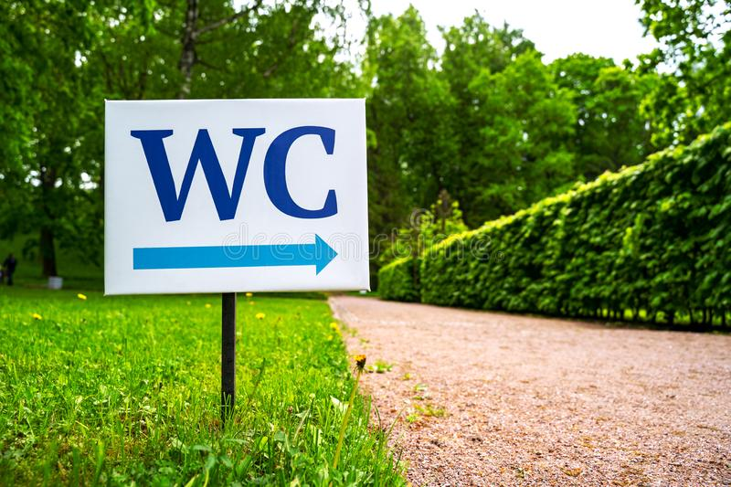 Toilet sign against the background of green trees in the park.  White WC sign on white metal plate with blue pointing arrow indica stock images