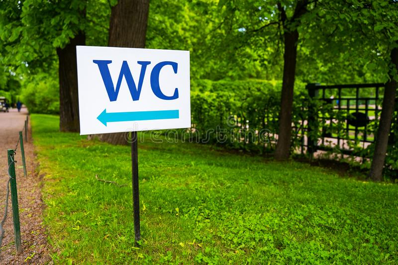 Toilet sign against the background of green trees in the park.  White WC sign on white metal plate with blue pointing arrow indica royalty free stock photography