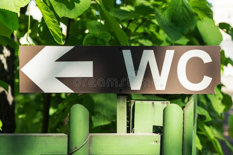 Toilet sign against the background of green trees in the park. White WC sign on brown metal plate royalty free stock photography