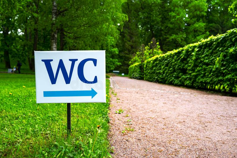 Toilet sign against the background of green trees in the park.  White WC sign on white metal plate with blue pointing arrow indica stock photo