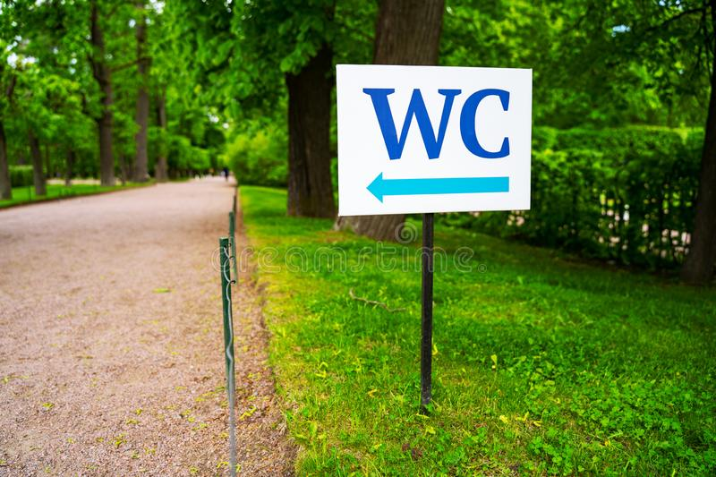Toilet sign against the background of green trees in the park.  White WC sign on white metal plate with blue pointing arrow indica royalty free stock photo