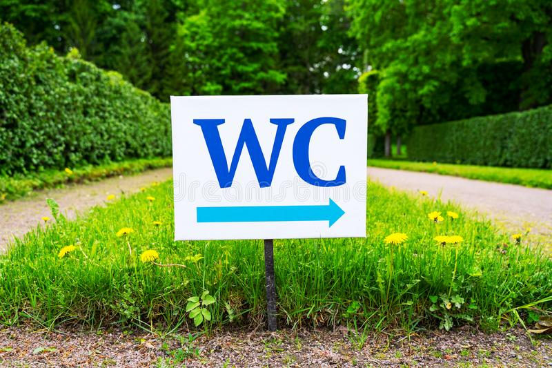 Toilet sign against the background of green trees in the park.  White WC sign on white metal plate with blue pointing arrow indica stock photography