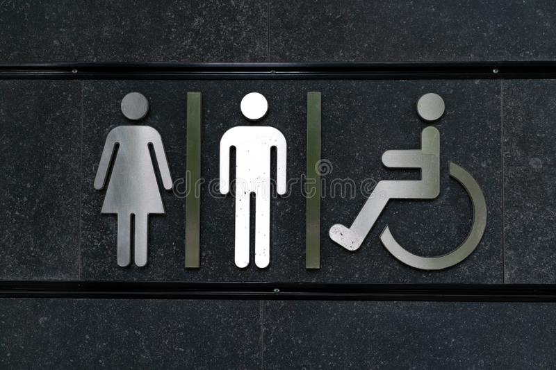 Toilet sign for male female and disabled people. Toilet sign male female disabled people shiny metal against black dark background. Public restroom signs. W stock images