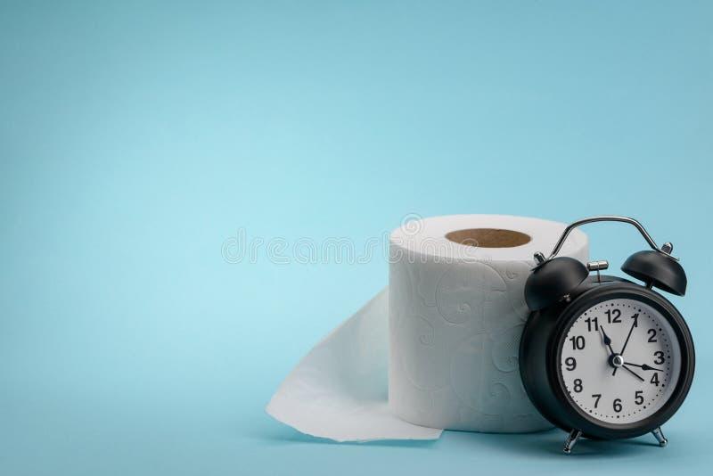 Toiletpapier en wekker stock afbeeldingen