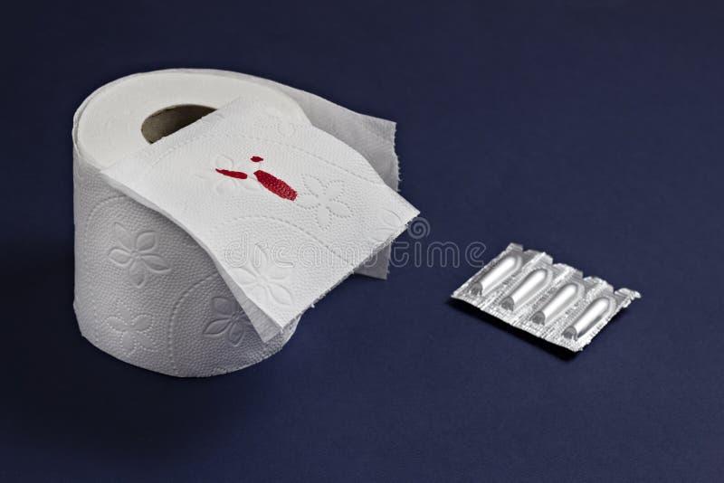 Toiletpapier met bloed en rectale zetpillen tegen hemorroïden, blauwe constipatie als achtergrond stock afbeelding