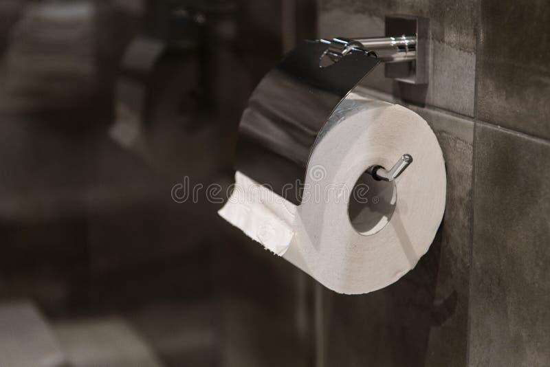 Toiletpapierbroodje in badkamers tegen grijze muurtegels royalty-vrije stock fotografie