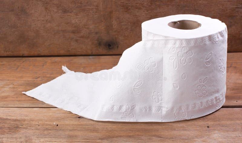 Toiletpapierbroodje, dat op een houten bureau rust stock afbeeldingen