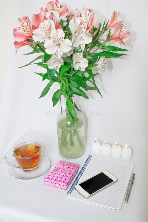 Toilettafel met vrouwen` s toebehoren Het beeld van een roze giftdoos met een boeket van Alstroemeria bloeit, romantische kaarsen royalty-vrije stock foto's