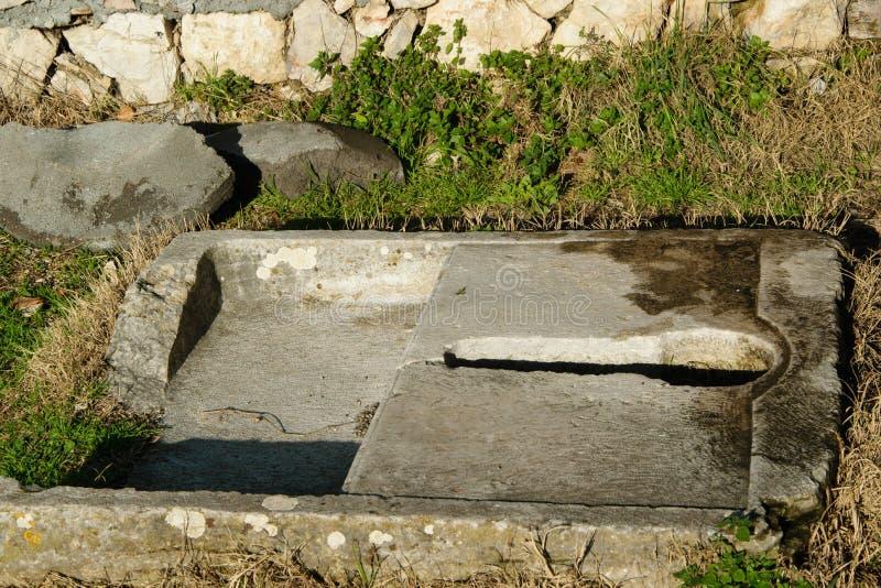 Toilette antica della pietra del privat immagine stock