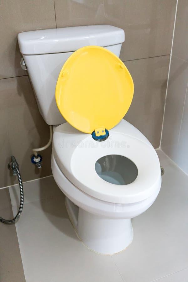 Toilette bianca con il sedile giallo del bambino fotografia stock libera da diritti