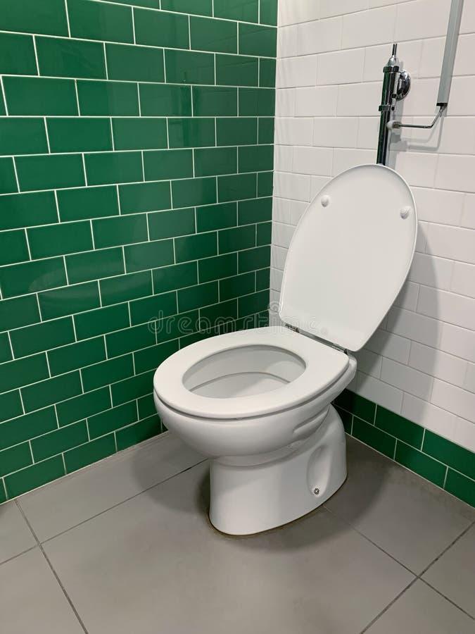Toilette blanche avec le couvercle ouvert près du mur images libres de droits