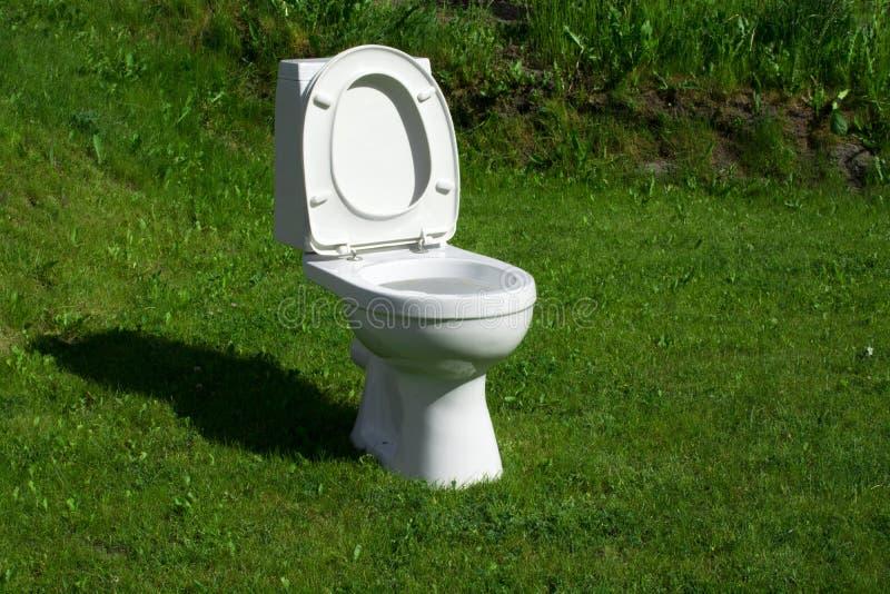 Toilette, die auf dem Rasen steht stockbild