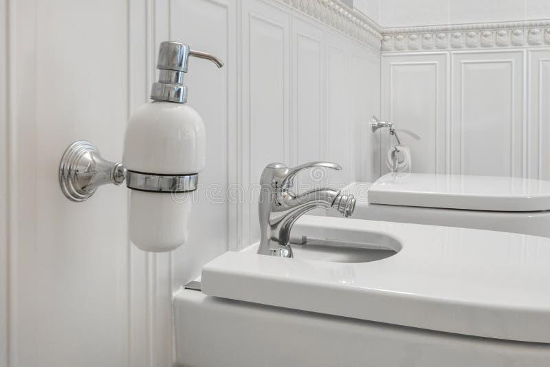 Toilette e dettaglio di un bidet d'angolo della doccia con gli erogatori dello sciampo e del sapone sul collegamento della doccia immagine stock