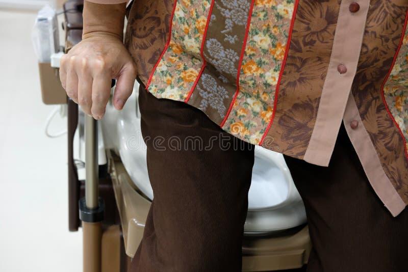 toilette en plastique mobile portative d'utilisation de dame âgée près de lit patient images stock