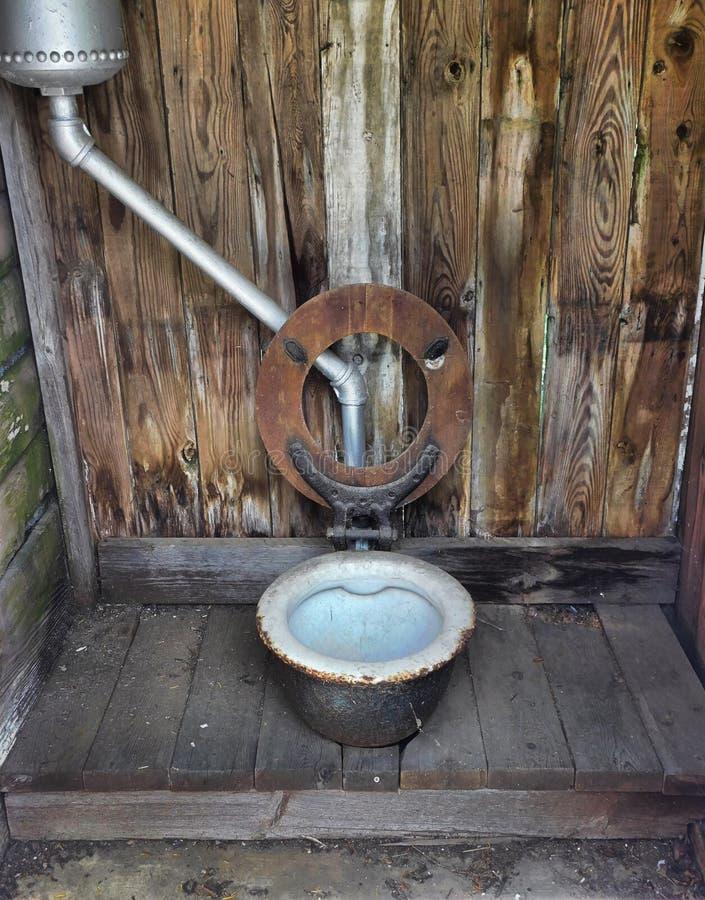 Toilette esterna alimentata dal mulino a vento immagine stock