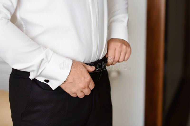 Toilette la préparation de matin, marié beau obtenant habillé et se préparant au mariage, utilisant une ceinture image libre de droits