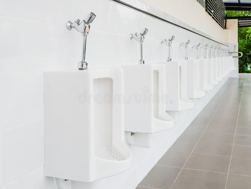Toilette masculine blanche moderne propre publique, toilettes avec des urinoirs photo stock