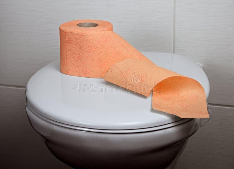 Toilette mit orange Toilettenpapier stockbilder