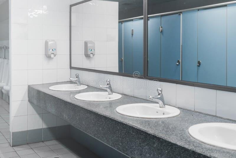 Toilette pubblica ed interno del bagno con il lavabo e la toilette r fotografia stock