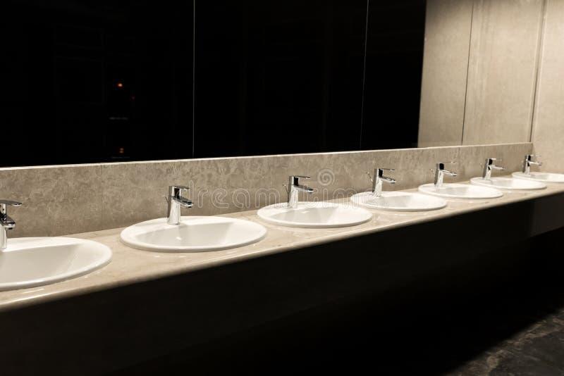 Toilette pubblica nel grandi specchio del ristorante e lotto dei portacatini fotografie stock
