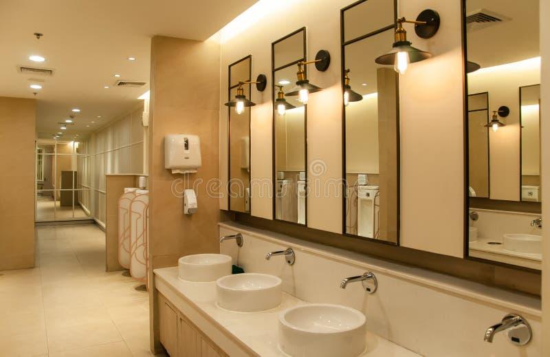 Toilette vuota pubblica dell'uomo con gli specchi di portacatini al grande magazzino centrale fotografia stock