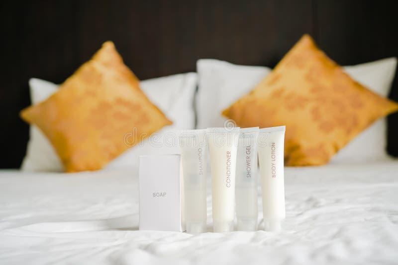 Toilettenartikel eingestellt auf Bett mit unscharfem Kissenhintergrund im Schlafzimmer lizenzfreie stockbilder
