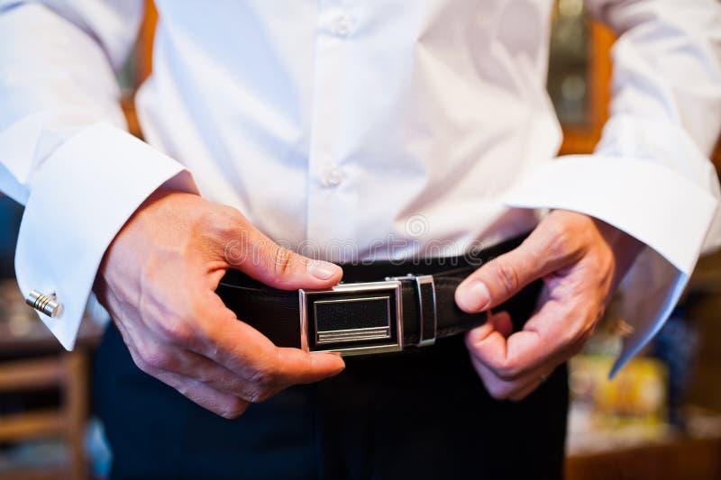 Toilettez attacher sa ceinture en cuir noire avant le ceremo de mariage photos stock