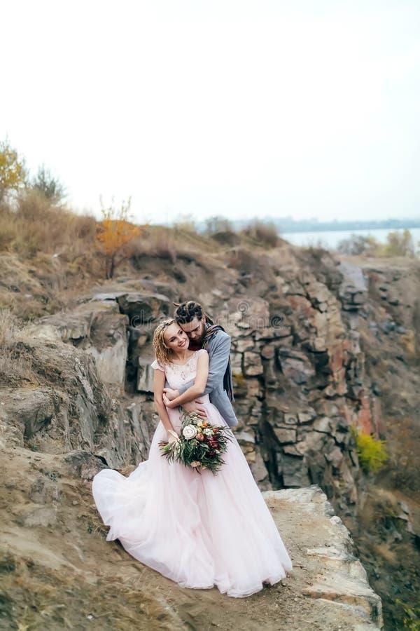 Toilettez embrasser tendrement sa belle jeune mariée par derrière Cérémonie de mariage d'automne dans le style rustique dehors Le photos libres de droits
