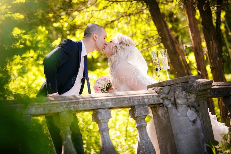Toilettez et la jeune mariée dans leur baiser de jour du mariage près d'une vieille balustrade image stock