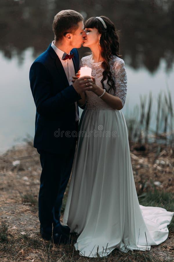 Toilettez et sa nouvelle épouse avec du charme embrassant sur le rivage du lac de forêt à la soirée image libre de droits