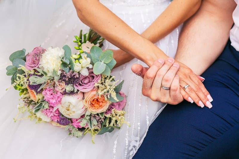 Toilettez l'étreinte la jeune mariée avec le beau bouquet de mariage photo stock