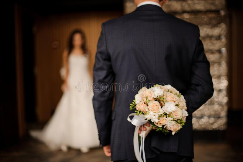 Toilettez la conservation derrière un bouquet des roses attendant la jeune mariée photos stock