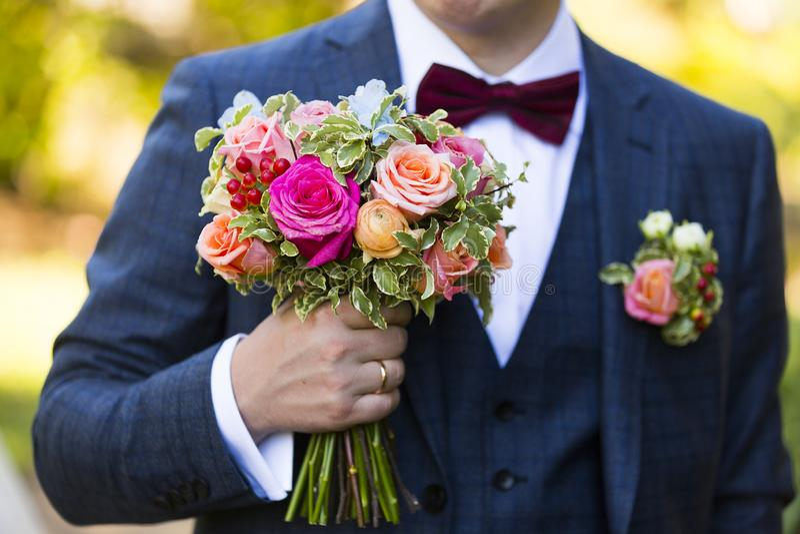 Toilettez le costume foncé de port de mariage avec le noeud papillon avec le bouquet de mariage images stock