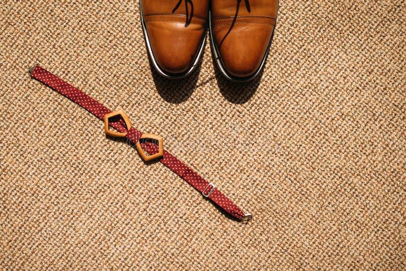Toilettez le noeud papillon et les chaussures du ` s sur le plancher image stock