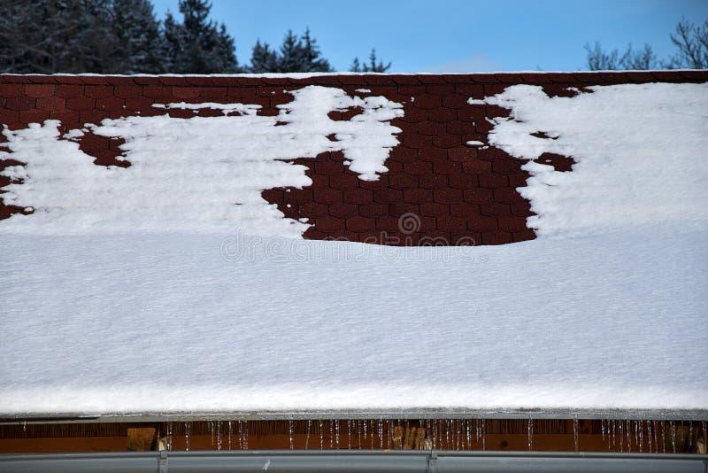Toit avec la gouttière de pluie en hiver Toit avec des bardeaux d'asphalte couverts de neige et de glaçons photos stock